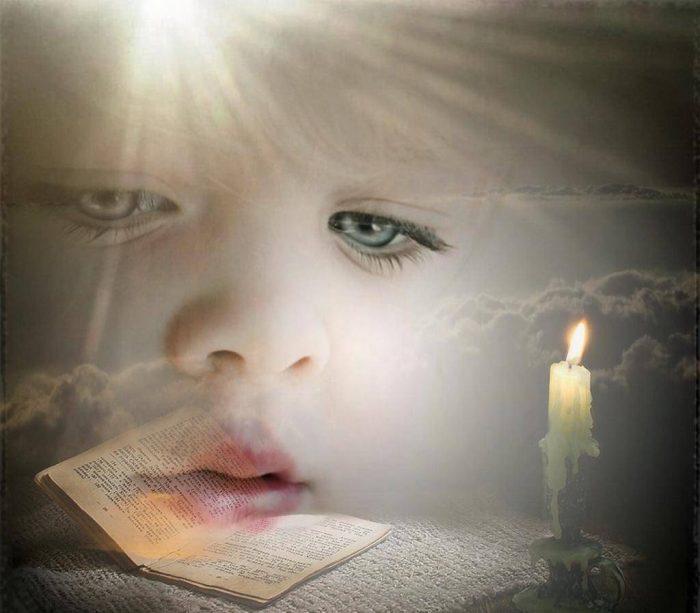 Лицо ребёнка на фоне горящей свечи и открытой книги
