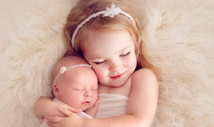 Маленькая девочка обнимает свою новорождённую сестричку